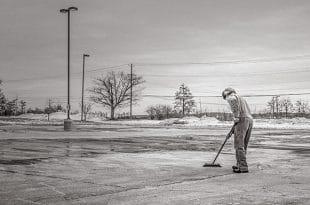 Une personne balayant un parking